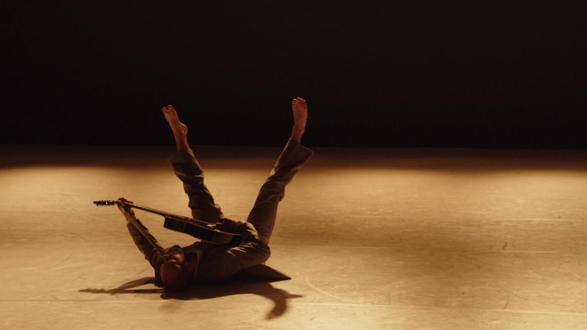 Dancer in suite with guitar lying on his back